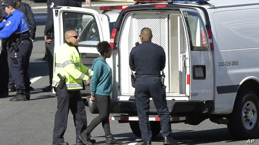 A woman, center, is taken into custody on Capitol Hill in Washington, March 29, 2017. Police say a driver struck a U.S. Capitol Police cruiser near the U.S. Capitol and was taken into custody.