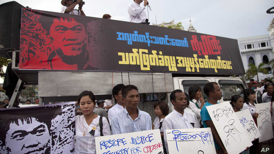 FILE - Activists hold placards during a protest against the killing of Aung Kyaw Naing, a freelance journalist, outside the city hall in Yangon, Myanmar.