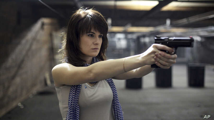 FILE - Maria Butina, a gun-rights activist poses for a photo at a shooting range in Moscow, Russia, April 22, 2012.