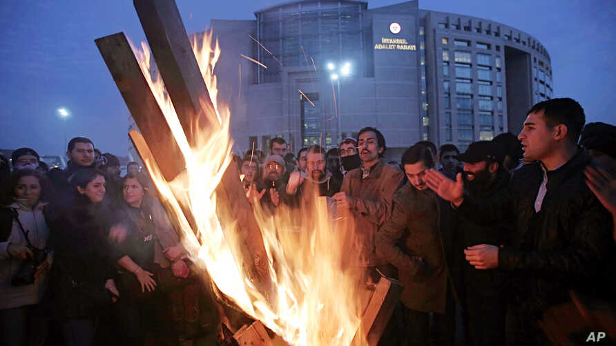 Cheering fans of the Besiktas soccer team gather around a fire outside a courthouse as a trial of dozens of football fans proceeds inside in Istanbul, Dec. 16, 2014.