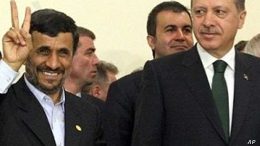Iran's President Mahmoud Ahmadinejad flashes the V-sign for victory as Turkish Prime Minister Recep Tayyip Erdogan looks on after the Islamic republic inked a nuclear fuel swap deal in Tehran (File Photo - 17 May 2010)