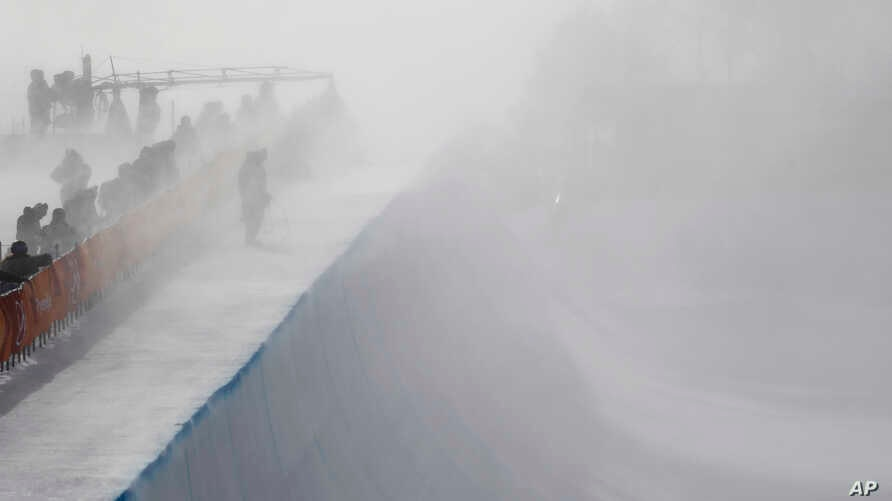 Wind gust engulfs the half pipe course during the women's halfpipe qualifying at Phoenix Snow Park at the 2018 Winter Olympics in Pyeongchang, South Korea, Feb. 12, 2018.