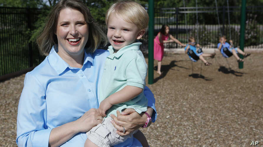 Christy Wolford, a breast cancer survivor, holds her youngest son Lucas, 2, as her other children play on the swing in the background  in Fort Collins, Colo. Wolford's ovaries were suppressed during cancer treatment and she has had three boys since i