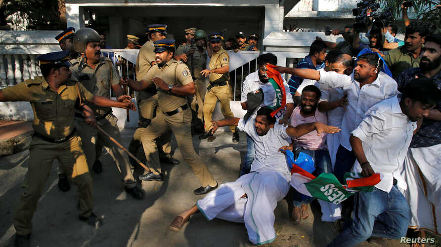 A police officer wields his stick against the members of Kerala Students Union, the student wing of India's main opposition Congress party, outside a police station during a protest in Kochi, India, Jan. 3, 2019.