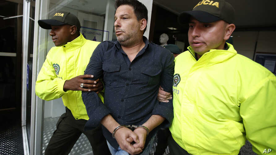 Police escort Cuban suspect Raul Gutierrez to court, where a judge will rule on prosecutors' request he be held on terrorism and conspiracy charges, in Bogota, Colombia, March 15, 2018.