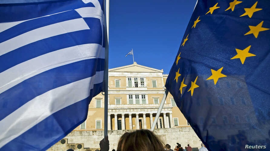 A woman waves a Greek national flag and a European Union flag during a rally outside the parliament, calling on the government to clinch a deal with its international creditors and secure Greece's future in the Eurozone, in Athens, Greece, June 18, 2