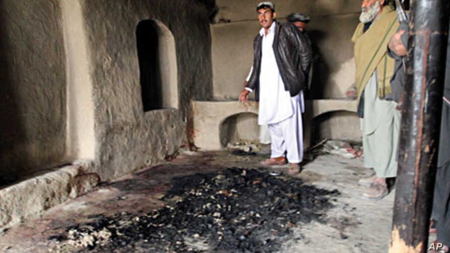 Men stand next to blood stains and charred remains inside a home where witnesses say Afghans were killed by a U.S. soldier in Panjwai, Kandahar province, south of Kabul, Afghanistan, March 11, 2012