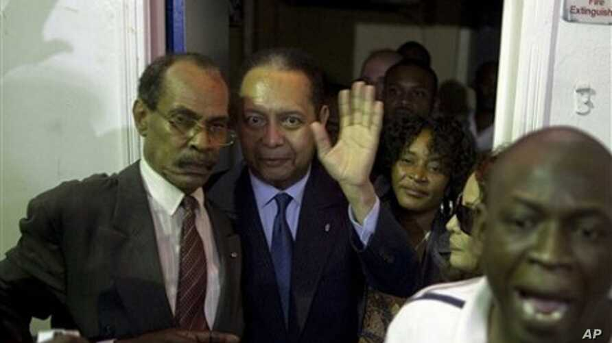 """Haiti's former dictator Jean-Claude """"Baby-Doc"""" Duvalier, center, waves to the media upon his arrival at the Toussaint Louverture international airport in Port-au-Prince, Haiti, 16 Jan. 2011."""