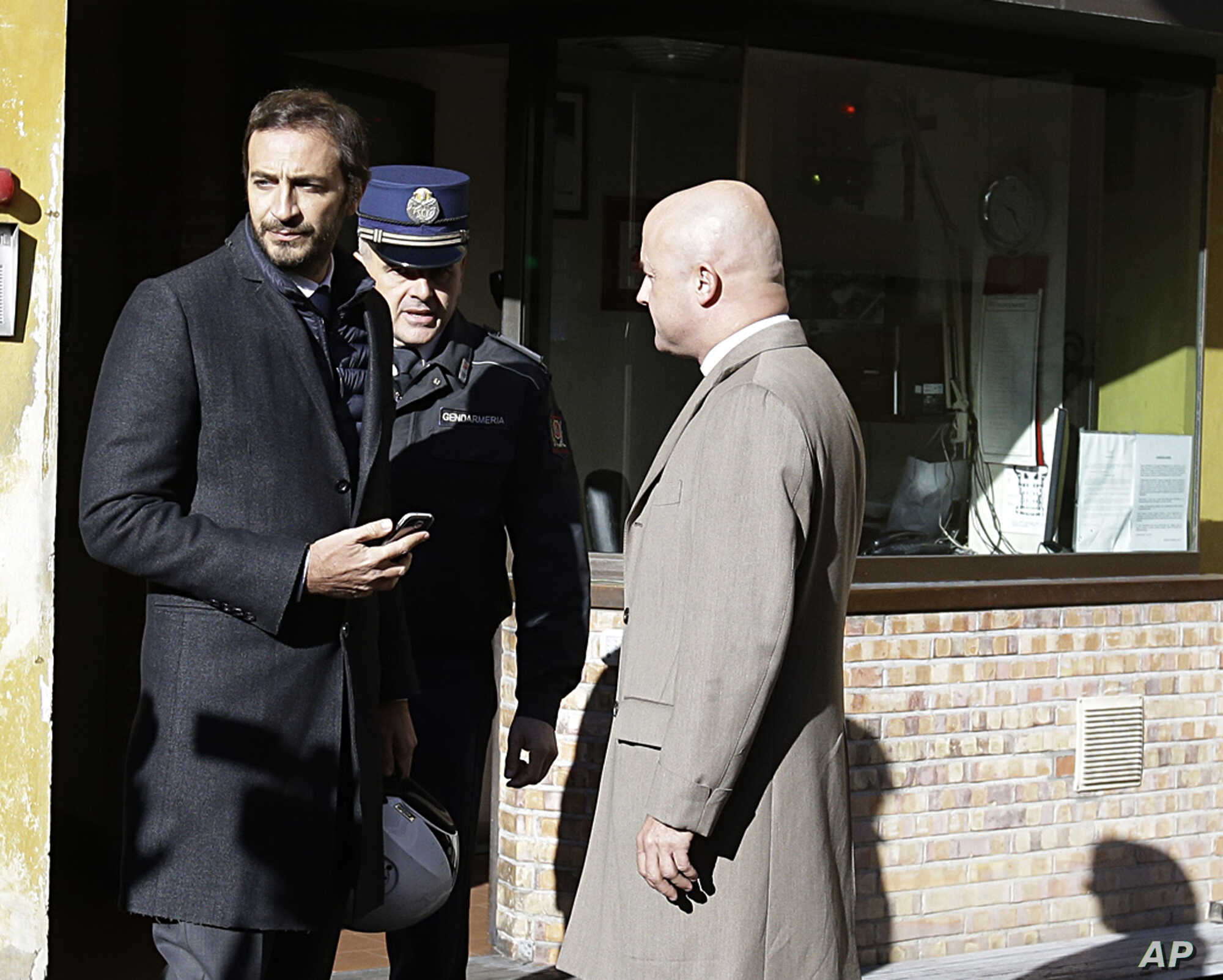 Italian journalists Gianluigi Nuzzi, right, and Emiliano Fittipaldi, left, talk with a Vatican Gendarmie guard at the Perugino entrance of the Vatican, Nov. 24, 2015.
