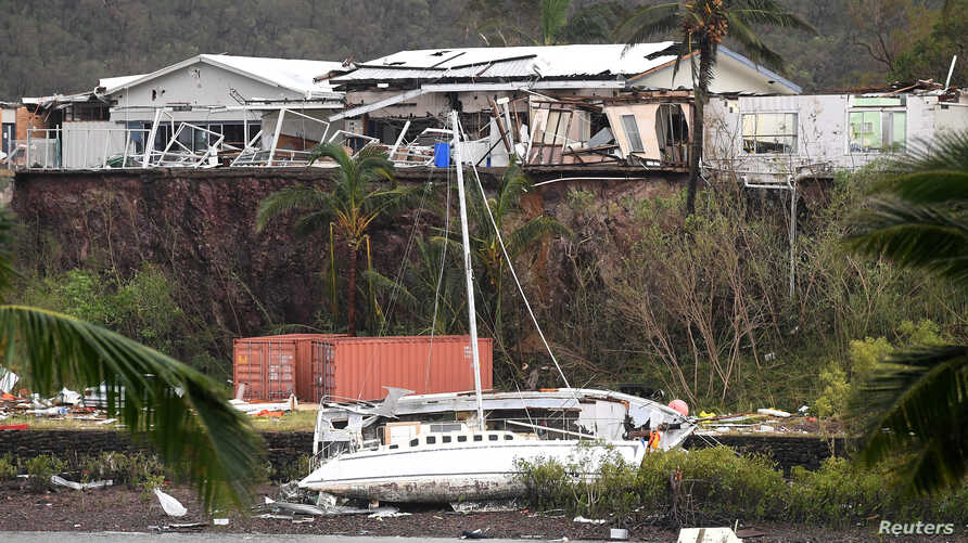 A damaged building is seen behind a boat that was pushed onto a bank by Cyclone Debbie in the township of Airlie Beach, located south of the northern Australian city of Townsville, March 29, 2017.