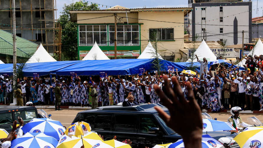"Cameroonian President Paul Biya, center, waves to supporters from his motorcade as he celebrates his re-election in Yaoundé, Nov. 6, 2018. He vowed to pursue policies of decentralization to address ""frustrations and aspirations"" in English-speaking r"
