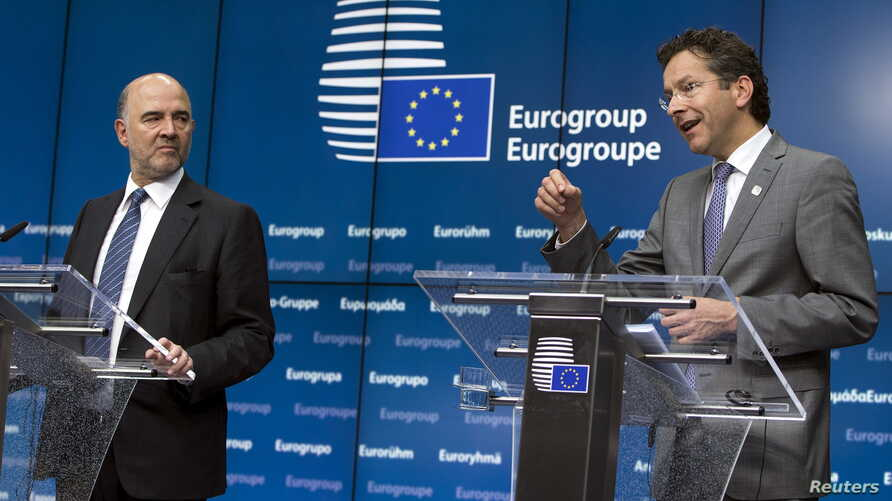 European Economic and Monetary Affairs Commissioner Pierre Moscovici (L) and Eurogroup President Jeroen Dijsselbloem speak at a news conference after a Euro zone finance ministers emergency meeting on Greece in Brussels, Belgium, June 22, 2015.