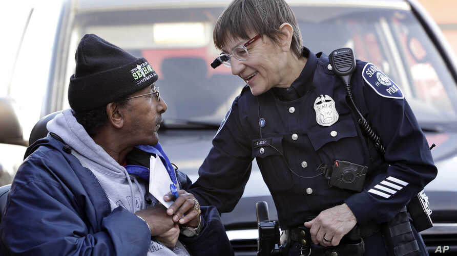 FILE - Seattle Police Officer Debra Pelich, right, wears a video camera on her eyeglasses as she talks with Alex Legesse before a community gathering in Seattle. While the Seattle Police Department bars officers from using real-time facial recognitio