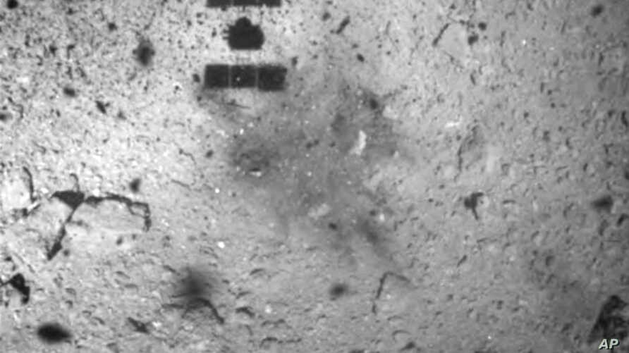 FILE - In this Feb. 22, 2019, file photo, this image released by the Japan Aerospace Exploration Agency (JAXA) shows the shadow, center above, of the Hayabusa2 spacecraft after its successful touchdown on the asteroid Ryugu.