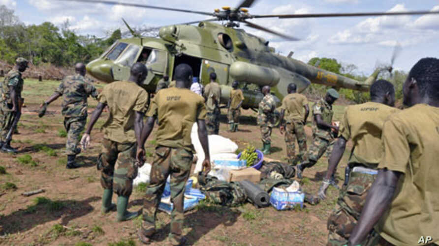 Ugandan soldiers, who are tracking down Lord's Resistance Army (LRA) fugitive leaders, load supplies off a military helicopter in a forest bordering Central African Republic, South Sudan and Democratic Republic of Congo, near river Chinko, April 18,