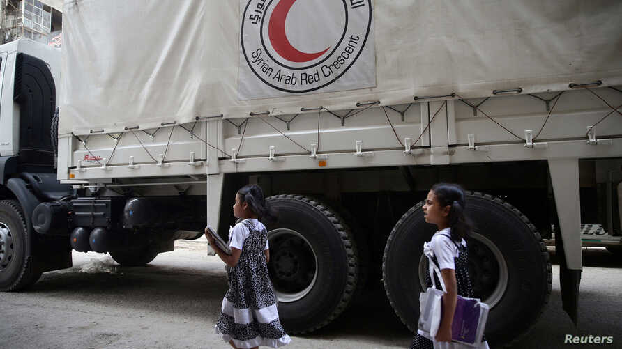 Twin girls walk near a Red Crescent aid convoy carrying urgent medical supplies in the rebel held besieged town of Douma, eastern Ghouta in Damascus, Syria, May 26, 2016.