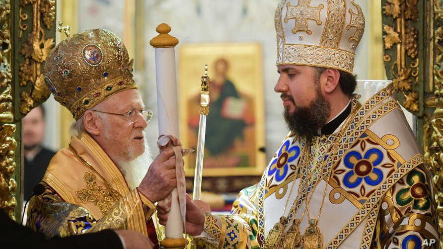 """Ecumenical Patriarch Bartholomew I, left, presents the """"Tomos,"""" in a symbolic ceremony sanctifying the Ukrainian church's independence from the Russian Orthodox Church to Metropolitan Epiphanius, the head of the independent Ukrainian Orthodox Church,"""