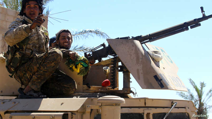 FILE - A fighter of the Syrian Democratic Forces gestures in the village of Baghuz, Deir el-Zour province, Syria, March 18, 2019.