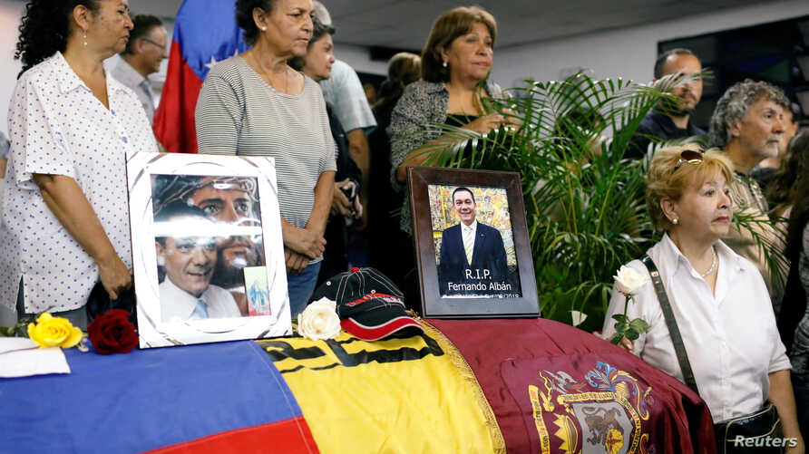 Mourners stand next to the coffin of the opposition lawmaker Fernando Alban during his wake in Caracas, Venezuela, Oct. 10, 2018.