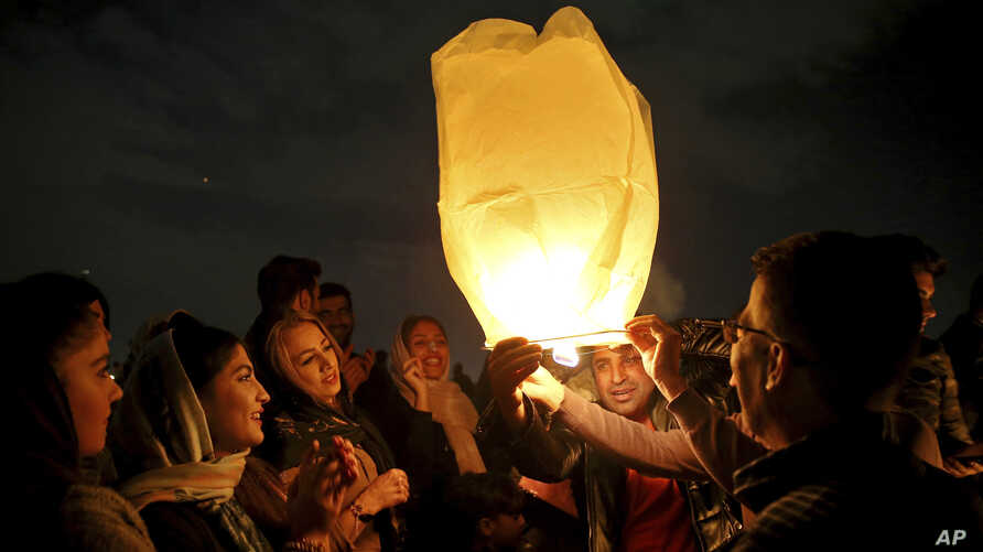 "Iranians release a lit lantern during a celebration, known as ""Chaharshanbe Souri,"" or Wednesday Feast, March 19, 2019, marking the eve of the last Wednesday of the solar Persian year, in Tehran."
