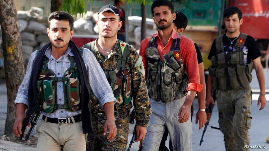 Kurdish fighters from the Popular Protection Units (YPG)  walk along a street in Aleppo, June 7, 2013, where they have joined the Free Syrian Army to fight against forces loyal to Syria's President Bashar al-Assad.