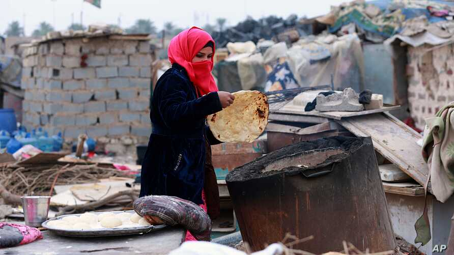 Umm Salem bakes bread in front of her hut at an encampment for the displaced outside Baghdad, Iraq, Feb. 12, 2018.