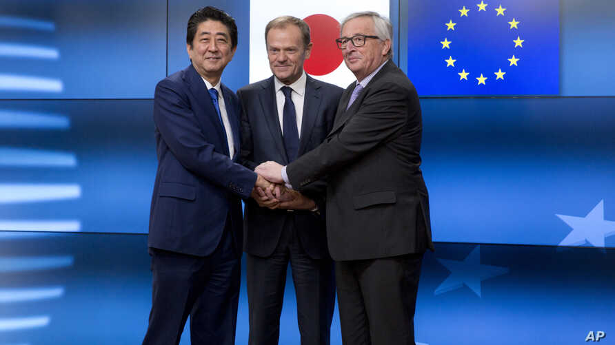 European Commission President Jean-Claude Juncker, right, European Council President Donald Tusk, center, greet Japanese Prime Minister Shinzo Abe prior to a meeting at the Europa building in Brussels on Tuesday, March 21, 2017.