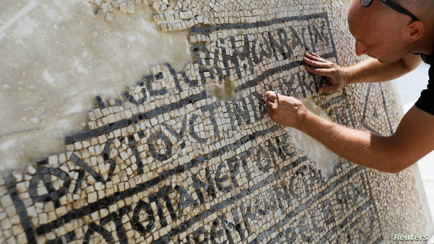 A conservationist works on a 1,500-year-old mosaic floor bearing Greek writing, discovered near Damascus Gate in Jerusalem's Old City, as it is displayed at the Rockefeller Museum in Jerusalem, Aug. 23, 2017.