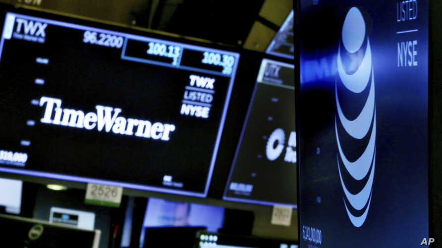 FILE - The logos for Time Warner and AT&T appear above alternate trading posts on the floor of the New York Stock Exchange, June 13, 2018.