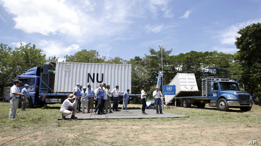 Colombia's President Juan Manuel Santos, right, talks with U.N. observers in front of containers holding weapons once carried by guerrillas of the Revolutionary Armed Forces of Colombia, FARC, at a demobilization site in Fonseca, Colombia, Aug. 15, 2
