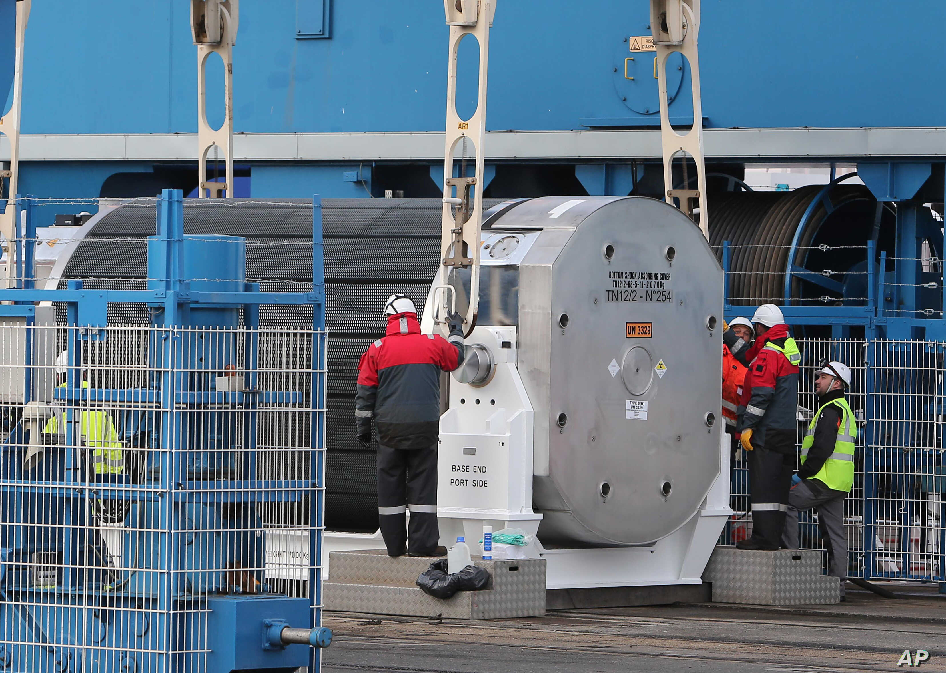 Harbour and Areva workers check a container carrying uranium oxide to make fuel pellets called MOX or mixed-oxide moment before being lifted onto the Pacific Egret cargo in Cherbourg harbor, western France, before heading for Japan, April 17, 2013.