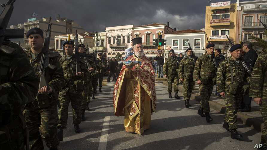 An Orthodox priest holds a cross as he is accompanied by a guard of honour during an Epiphany ceremony to bless the water in Mytilene port on the northeastern Greek island of Lesbos, Jan. 6, 2016.