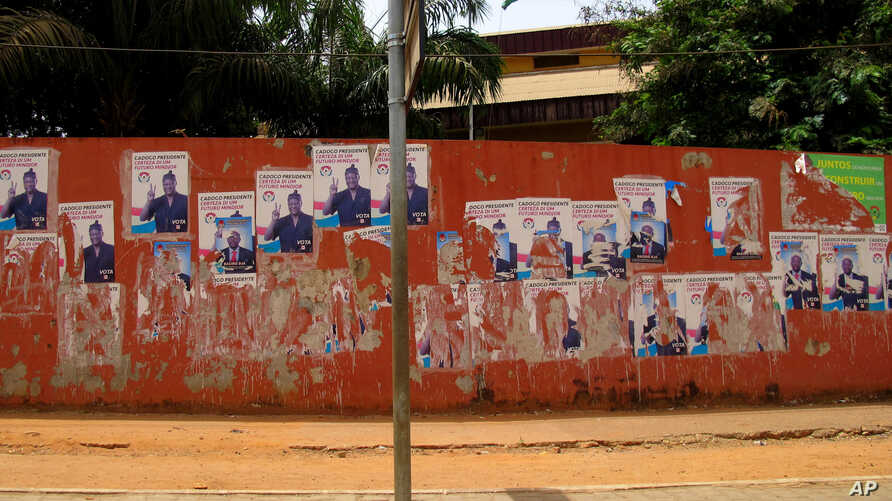 Torn election campaign posters depicting Carlos Domingos Gomes Jr. line a main road in Bissau.