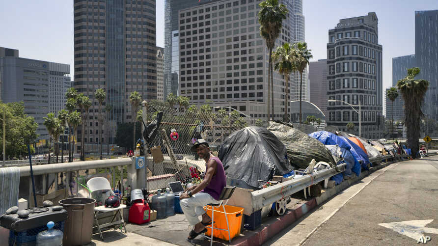 FILE - A homeless man sits at his street-side tent along Interstate 110 along downtown Los Angeles' skyline, May 10, 2018. Thousands of homeless people sleep on the streets of Los Angeles County. Southern California Public Radio station KPCC reports ...