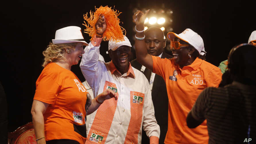 Ivory Coast incumbent President Alassane Ouattara, center, dances  with his wife Dominique Ouattara, left,  during his election rally  in Abidjan, Ivory Coast, Oct. 23, 2015.
