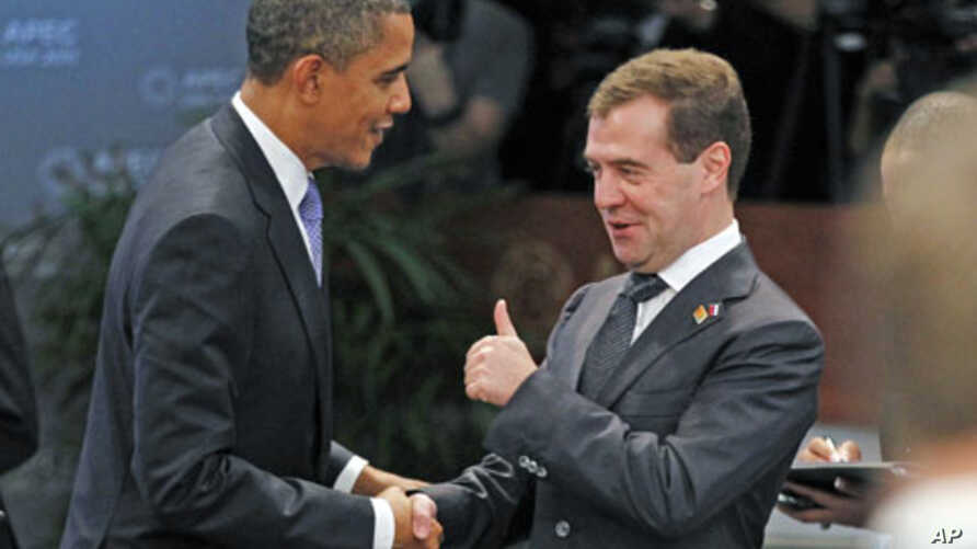 Russia's President Dmitry Medvedev (R) gives U.S. President Barack Obama a thumbs up as they meet at the first plenary meeting during the APEC Summit in Honolulu, Hawaii November 13, 2011.