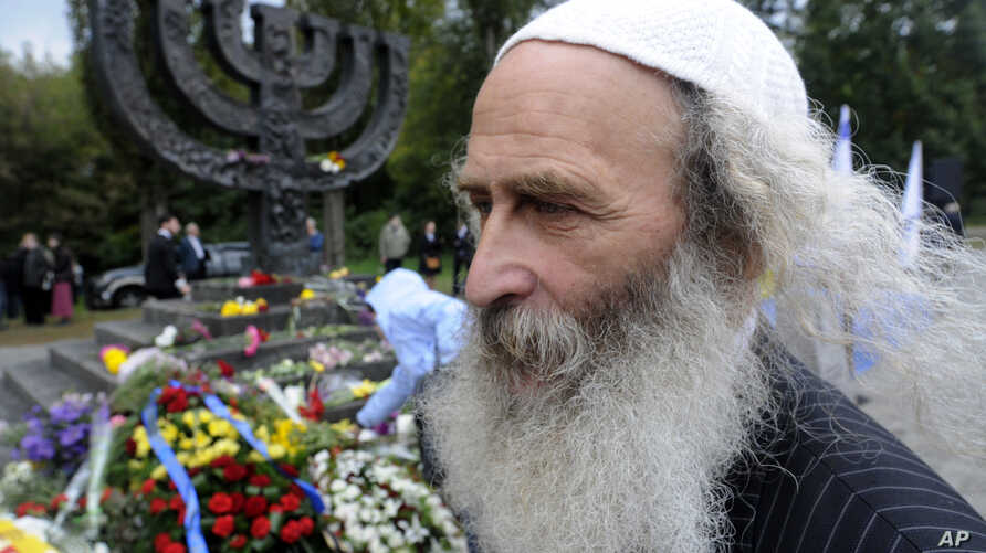 FILE - People lay flowers at a menorah monument close to the Babi Yar ravine where the Nazis machine-gunned tens of thousands of Jews during WWII, in Kyiv, Ukraine, Sept. 30, 2012.