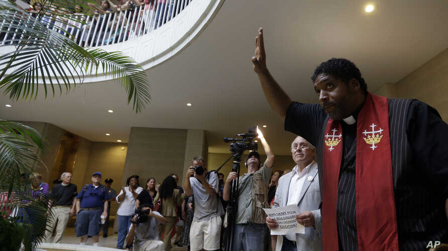 """FILE - Rev. William Barber, president of the North Carolina chapter of the NAACP, speaks to protesters and demonstrators outside the House and Senate chambers at the state legislature during the NAACP-led """"Moral Monday"""" protests at the General Assemb"""