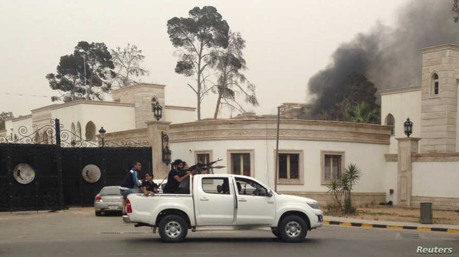 Armed men aim their weapons from a vehicle as smoke rises in the background near the Libyan parliament building in Tripoli May 18, 2014.
