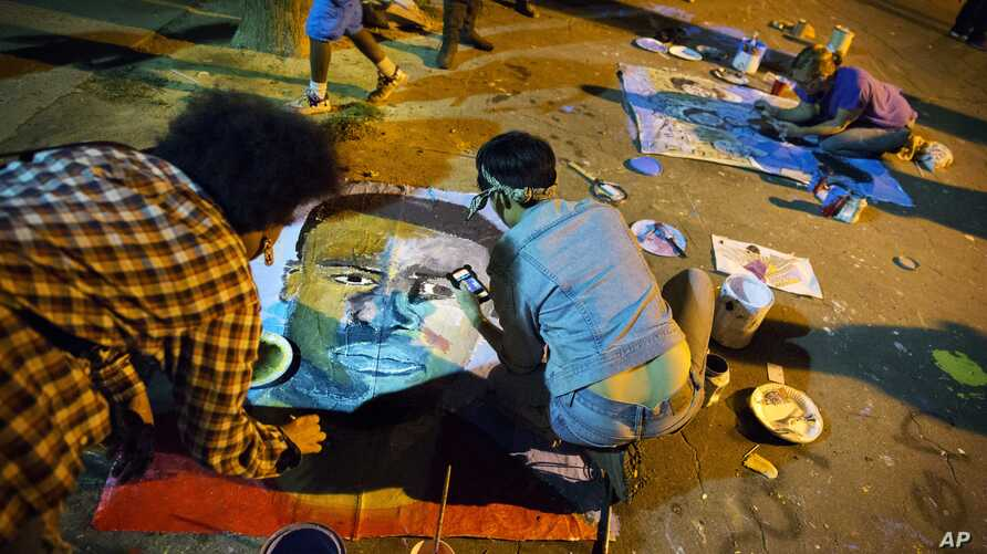 FILE - People paint a portrait of Freddie Gray at a housing complex where he was arrested, May 3, 2015, in Baltimore, Maryland.