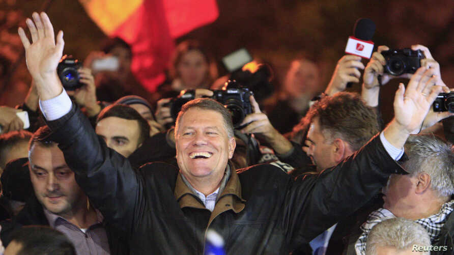 Romanian presidential candidate Klaus Iohannis celebrates his victory in the election run-off, with protesters in central Bucharest, November 16, 2014.