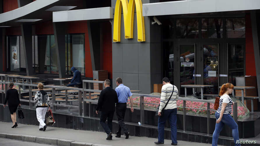 People walk past a closed McDonald's restaurant, one of four temporarily closed by the state food safety watchdog in Moscow, August 21, 2014