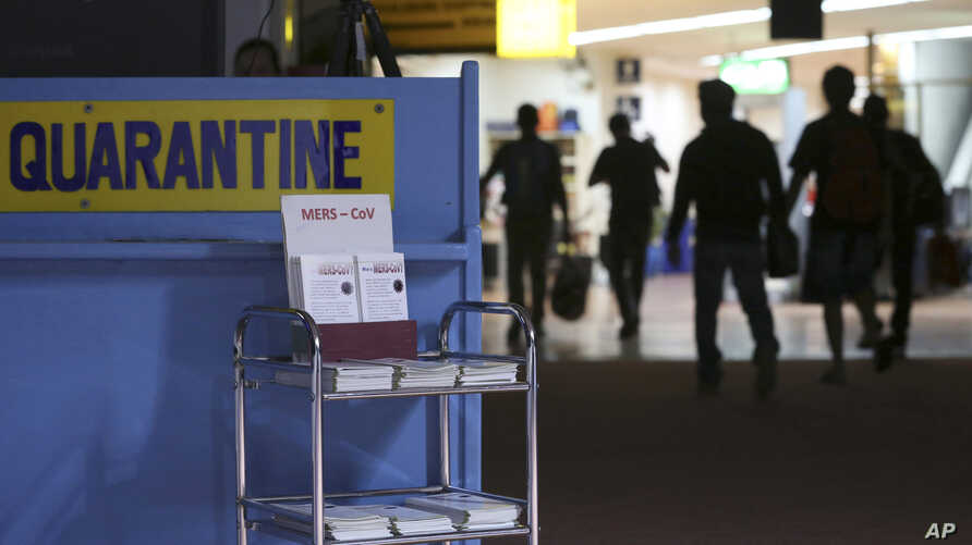 FILE - Passengers walk past the medical quarantine area showing information sheets for the Middle East respiratory syndrome coronavirus at the arrival section of Manila's International Airport in Paranaque, south of Manila, April 16, 2014..
