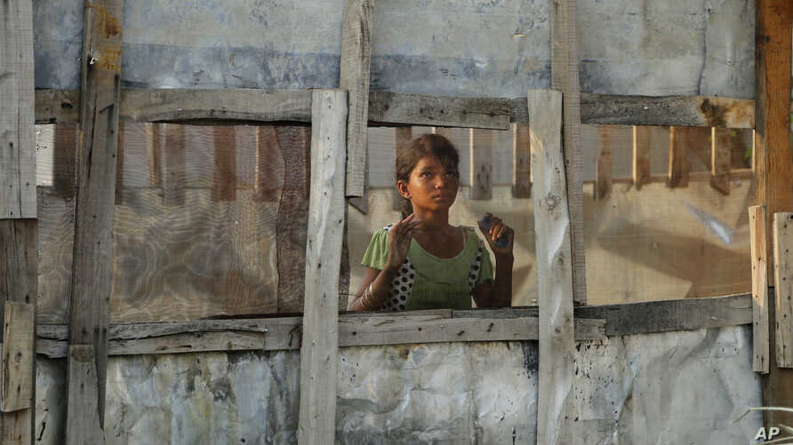 A Rohingya refugee girl looks through a mesh window at a camp set up for the refugees on the outskirts of Jammu, India, Aug. 16, 2017.