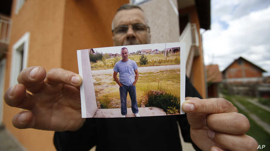Bosnian man Andjelko Djuric ,45, shows photos of his late brother Dragan Djuric police officer who was killed in Monday's attack at a police station, in the eastern Bosnian town of Zvornik, 200 kilometers (124 miles) east of Sarajevo, April 28, 2015.