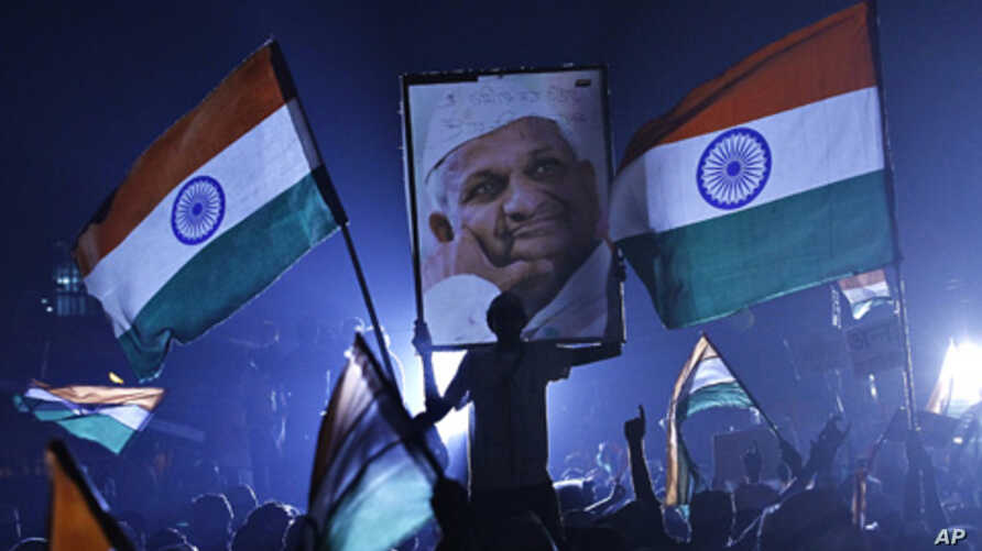 A supporter of veteran Indian social activist Anna Hazare holds his portrait on the ninth day of Hazare's fast at Ramlila grounds in New Delh,i Aug. 24, 2011.