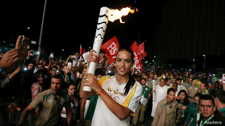 Model Adriana Lima carries the Olympic torch in Maua Square in Rio de Janeiro, Brazil, August 4, 2016.