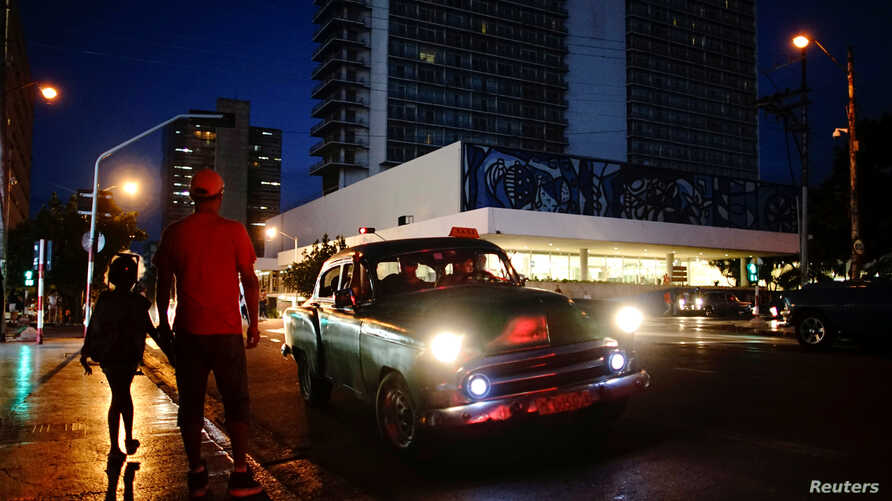 People wait on the sidewalk for transportation as a vintage U.S. car used as private taxi passes by in Havana, Cuba, Sept. 20, 2018.