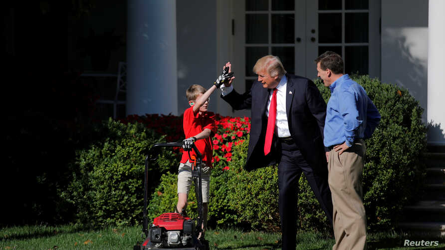 U.S. President Donald Trump welcomes Frank Giaccio, 11, as he cuts the Rose Garden grass at the White House in Washington, Sept. 15, 2017.
