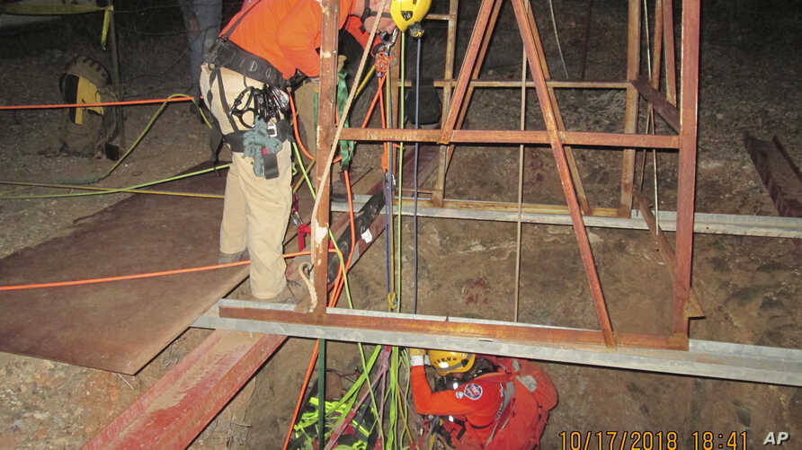 This Oct. 17, 2018, photo provided by the Maricopa County Sheriff's Office shows rescue team members lowering themselves into an abandoned mine shaft to rescue a man who fell into the shaft two days earlier, near Aguila, Ariz.